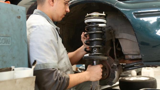 Técnico se prepara para instalar o amortecedor